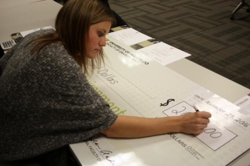 Woman writing out giant cheque