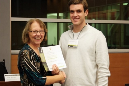 Woman smiling and handling certificate to male student in white sweater