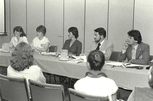 A group of students sitting on one side of a long table, in front of an audience.