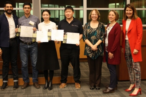 Three students with four judges hold certificates and smile