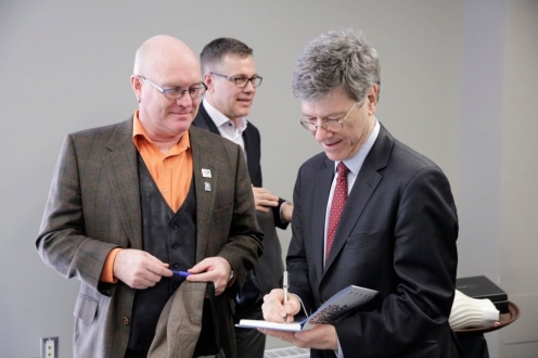 Man in grey suit signs book for man in suit with orange shirt