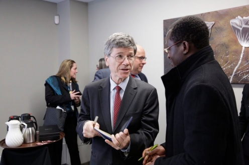 Man in grey suit chats with African man in black jacket
