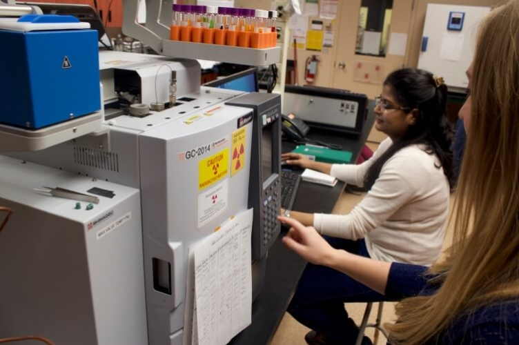 Student in foreground pushing buttons on front of large piece of lab equipment while student in background is on computer