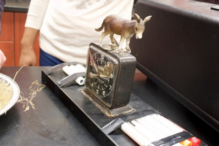 Donkey figurine on top of rusty antique clock