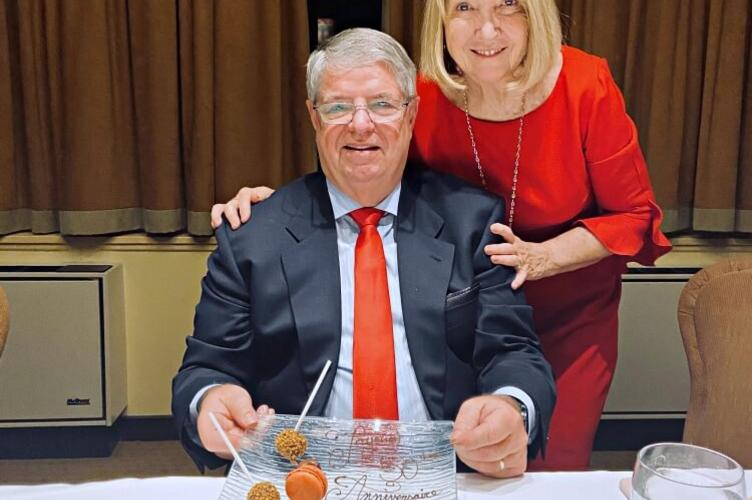 Couple posing with desserts on plate and 50th anniversary in icing