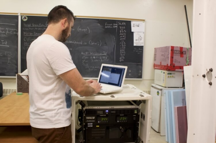 Student standing at laptop