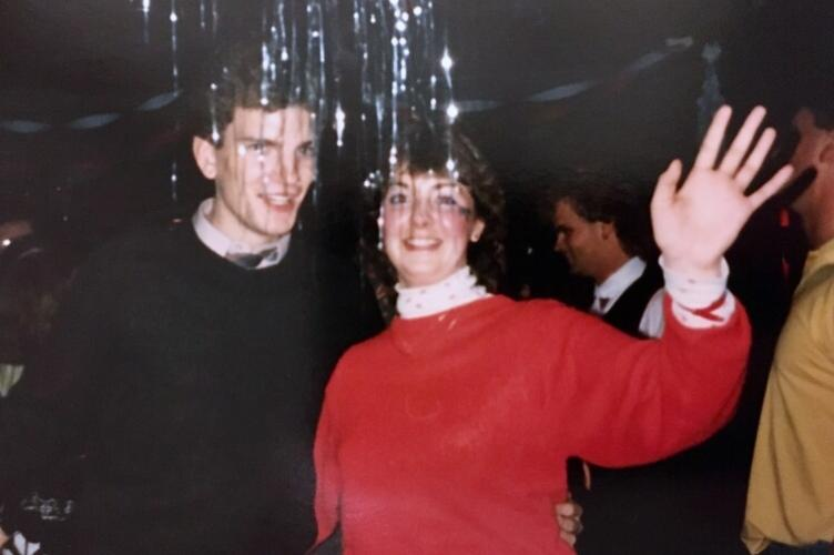 Two students at a dance waving