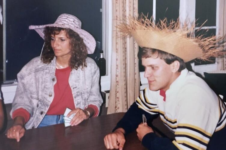 Two students in hats at a table playing cards