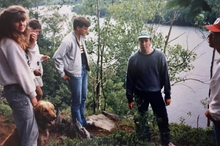 University students in the late 1980s standing on the edge of a lake