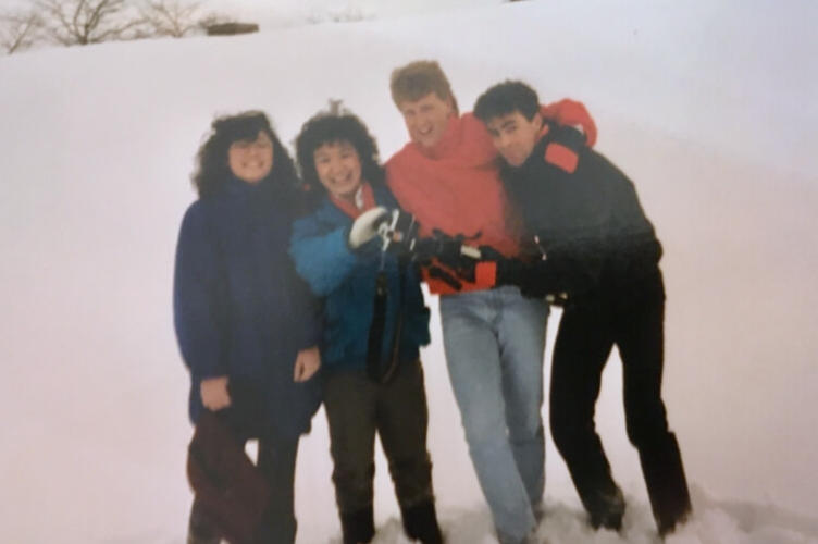 Four university students in the 80s standing in the snow