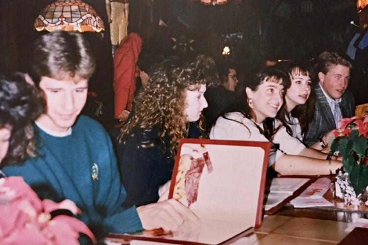 Group of late 80s university students at restaurant table looking at menu