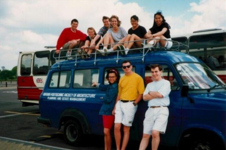 Students posed in front of and sitting on top of a blue van
