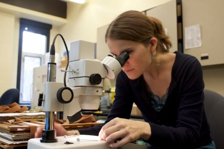 PhD student looking through microscope at plant sample