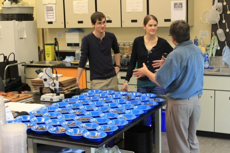 Professor in discussion with two grad students on far side of table, on which there is an array of blue trays full of samples