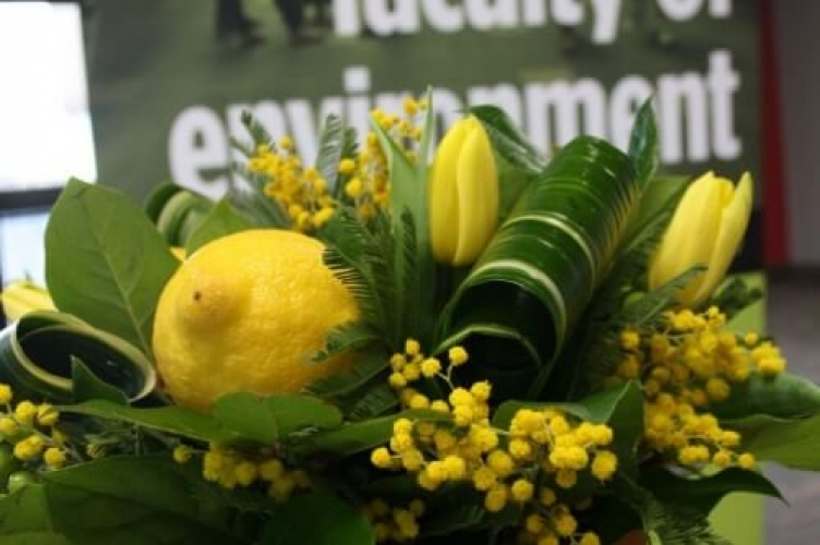 Floral bouquet with lemons in front to sign that says