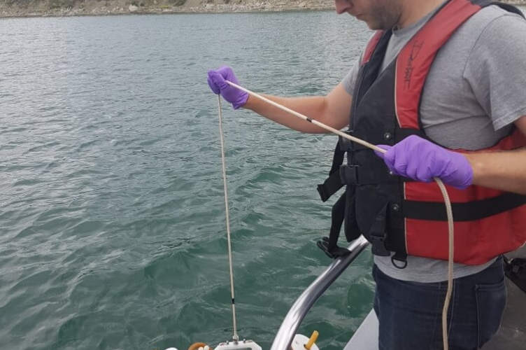 Student on edge of boat holding tube device over the water by a cord