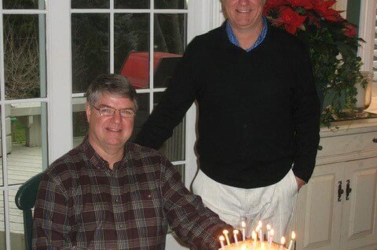 Two people with a birthday cake