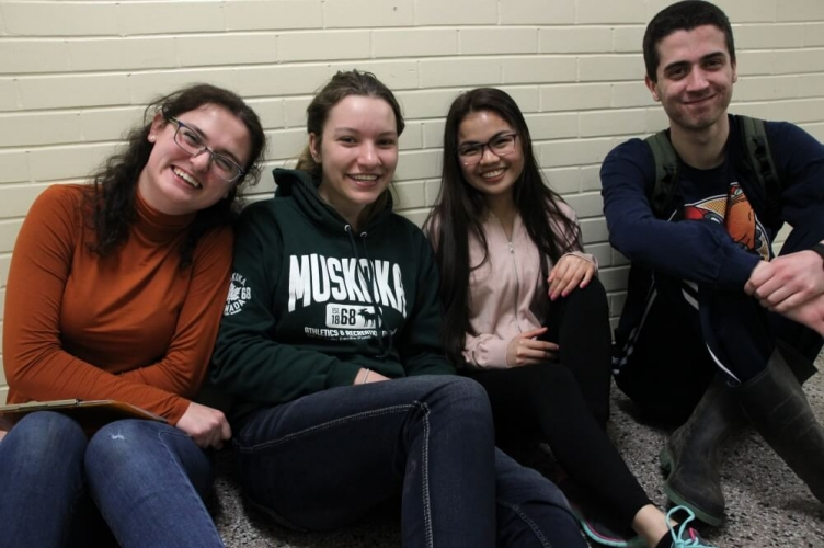 4 students, 3 girls and one boy, sitting against the wall smiling