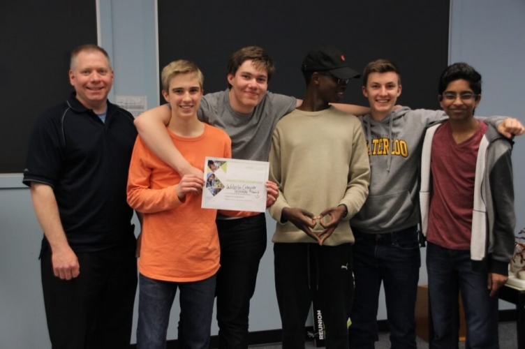 Diverse group of male students and their teacher smiling with certificate