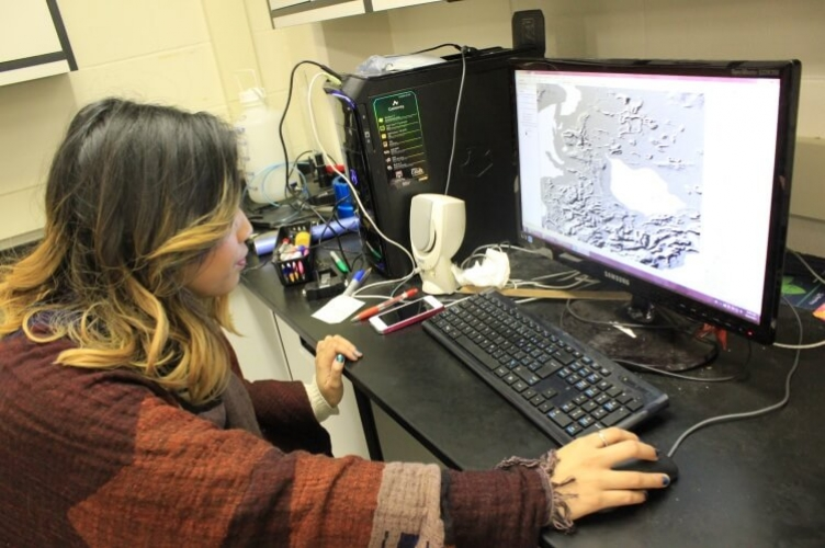 Student sits as computer screen displaying topographical map