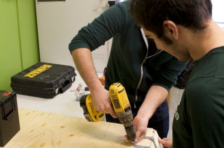 One student drilling hinge bracket to attach two pieces of wood, while another student holds on of the pieces