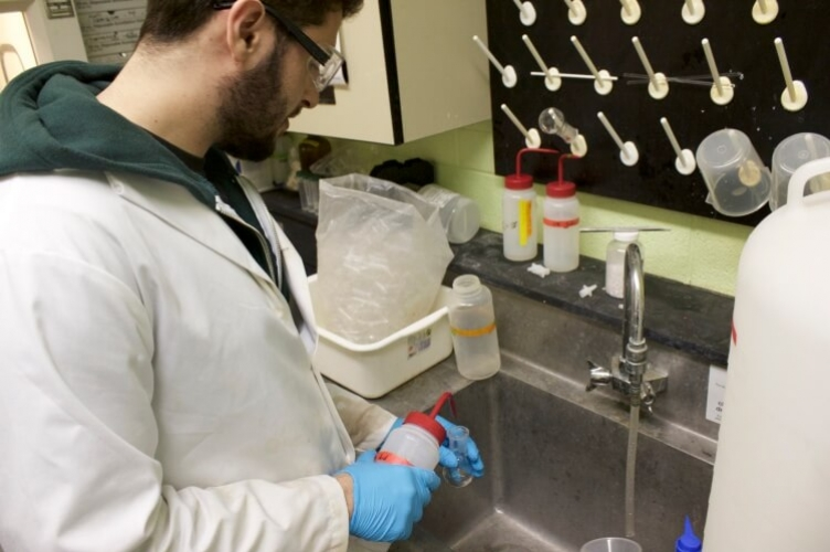 Student in lab coat standing at sink pipetting liquid into small test tube