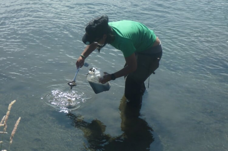 Student with green t-shirt and rubber boots standing in shallow water, scooping mud into a plastic jug