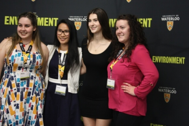 Four female students pose in front of step and repeat wall