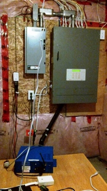 A small computer sits under a smart electrical panel and other equipment in a private home.