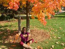 Kayla sitting in the autumn leaves under a tree