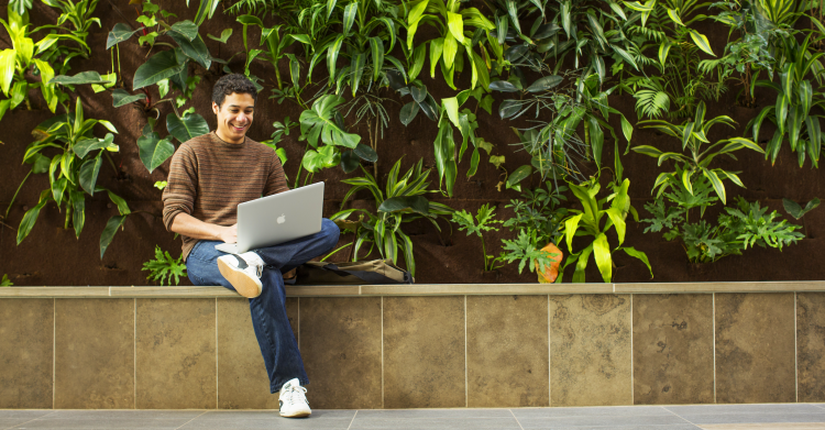 Student sitting by the living wall.