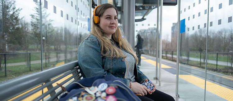 Miila, a third year Planning student, waits for public transit while listening to music through headphones.