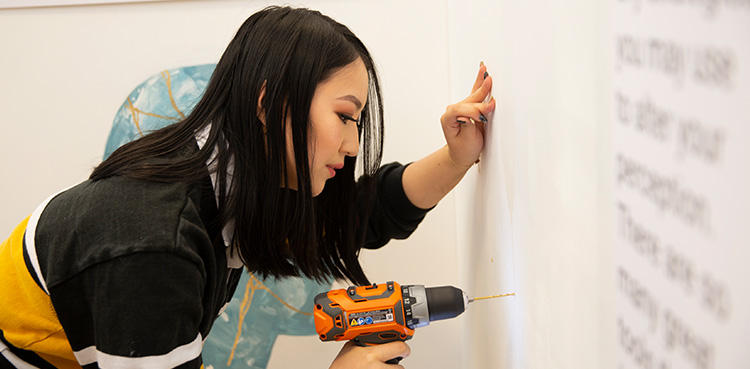 Victoria, a Knowledge Integration student, uses a drill while working on her team's museum exhibit