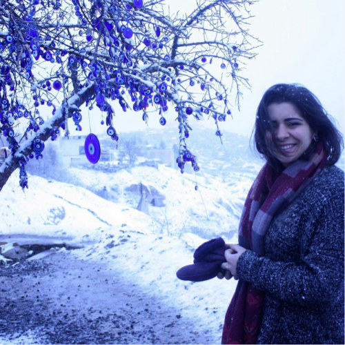 Co-op student Nataly Arar in front of tree in winter.