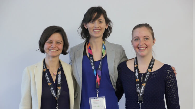 Three female grad students in business casual attire with their arms around one another's back