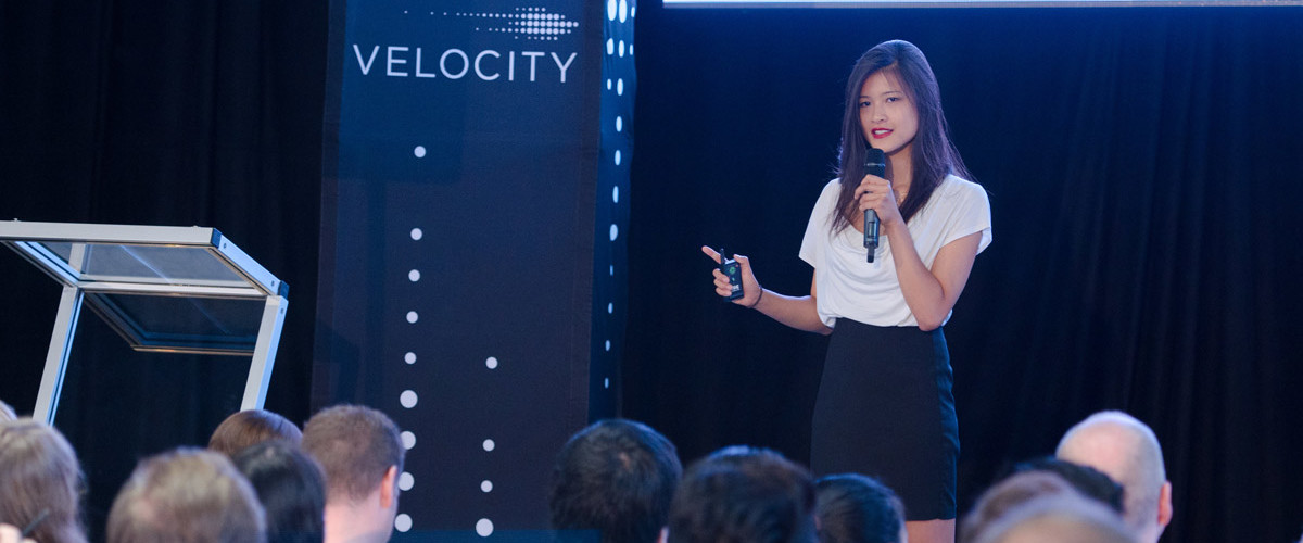 woman speaking into microphone at velocity event