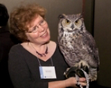 Middle-aged woman holds an owl.
