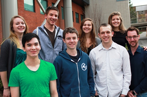 A group of eight students poses outside the Environment 3 building.