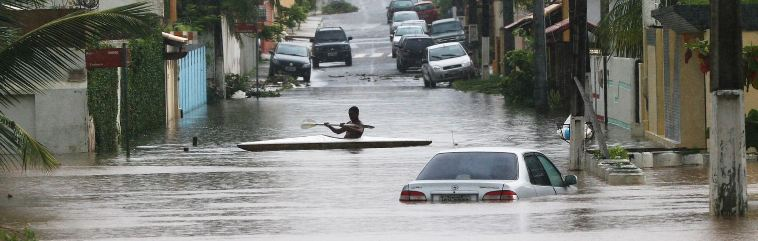 Man paddling a canoe through a flooded neighbourhood