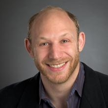 George Roter, a balding 30-something man in a suit.