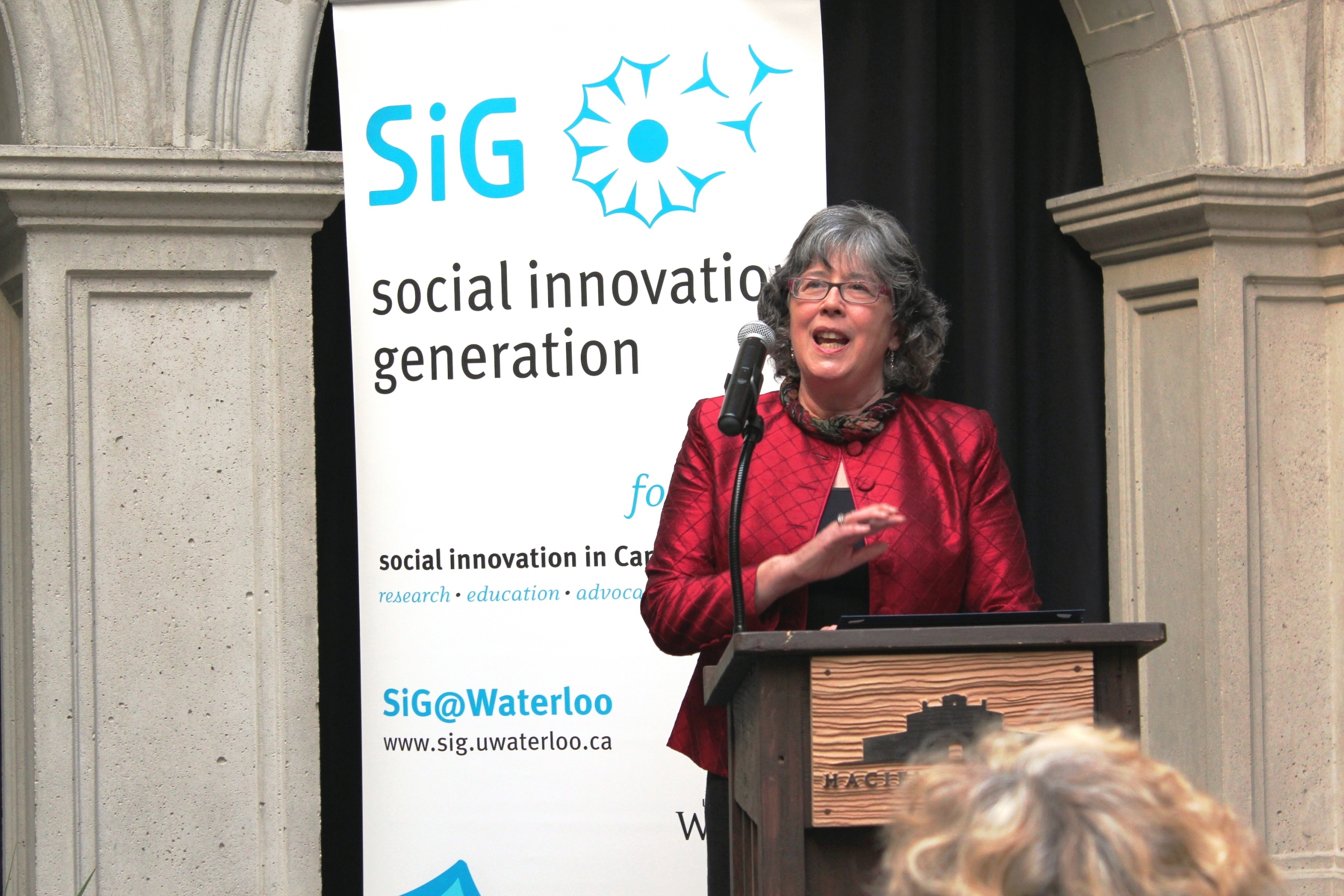 "Frances Westley speaks in front of banner reading ""SiG - Social Innovation Generation."""