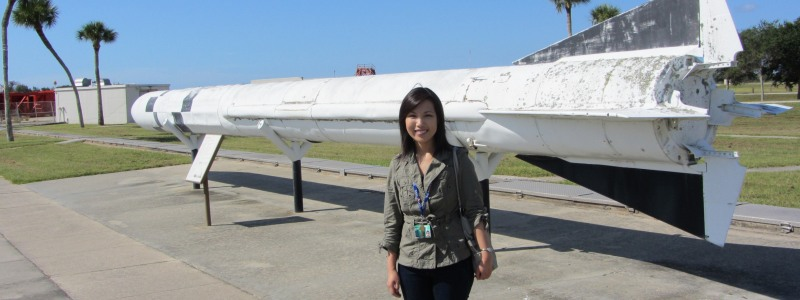 Su Yin standing in front of a large decommissioned rocket