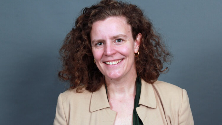 Amelia Clarke, professional headshot of woman with brown curly hair wearing beige jacket and green blouse