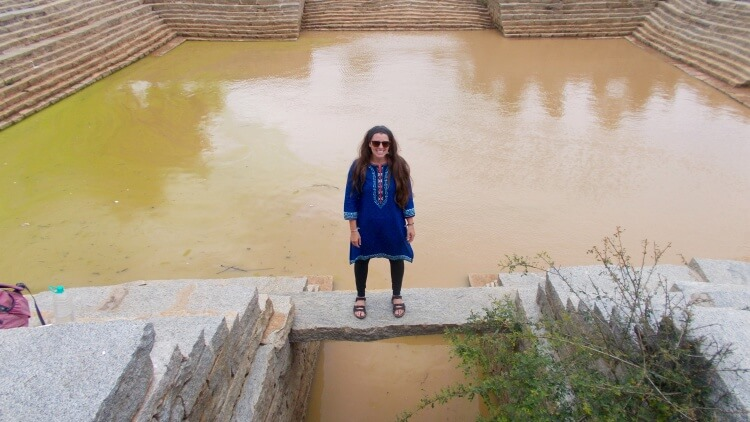 Woman wearing blue indian shirt stands in front of large water pit
