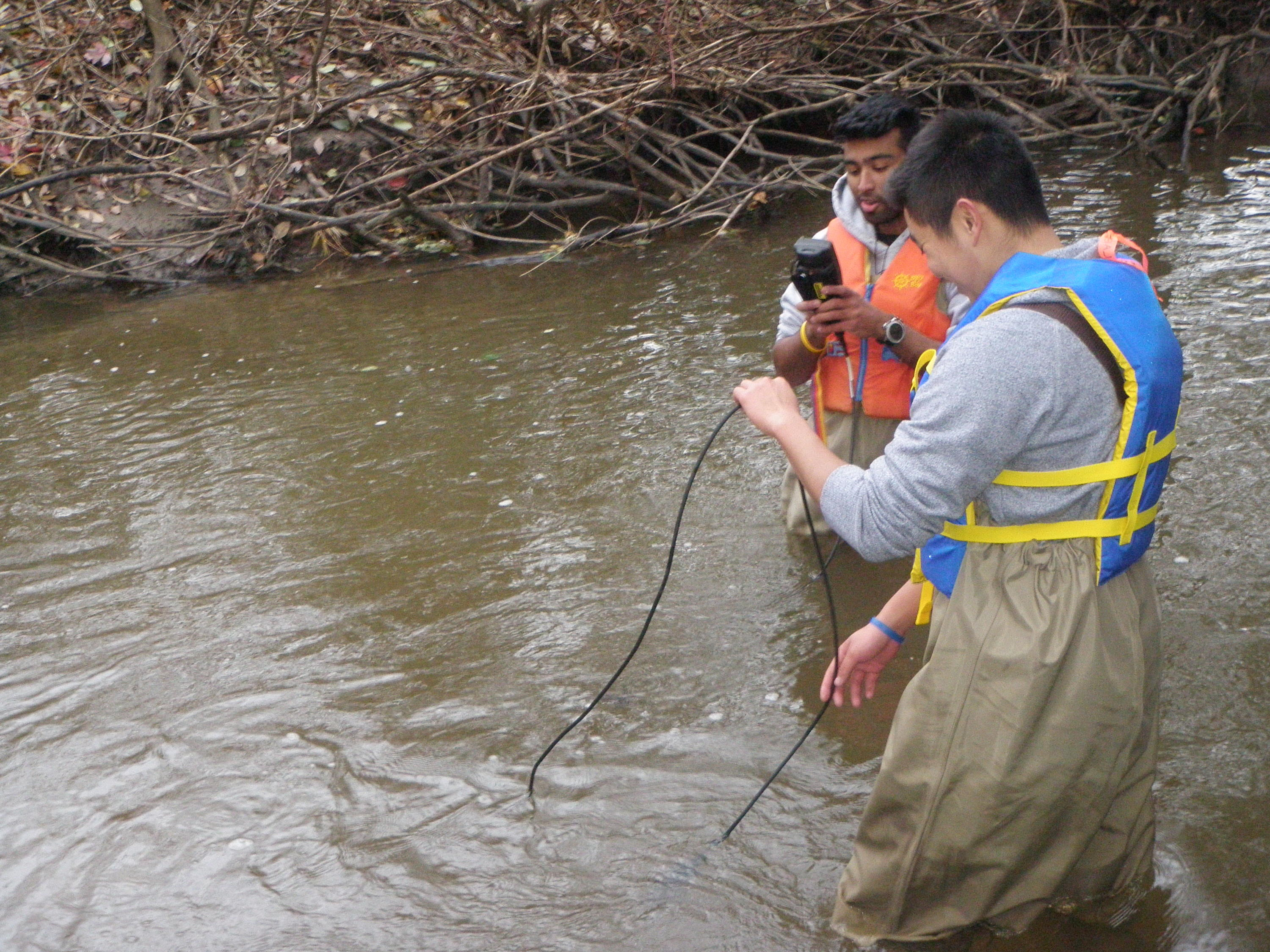 two students in a river using some equipment