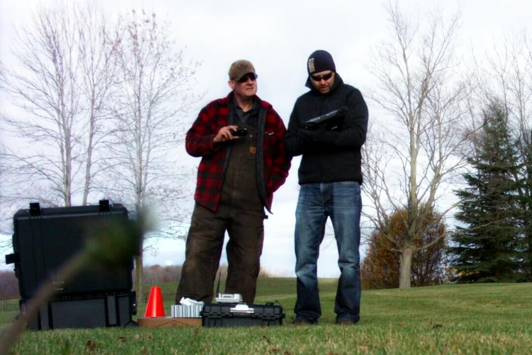 Two men looking at drone equipment, farmland and trees in background