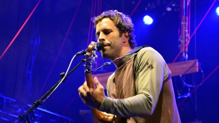 Musician Jack Johnson singing and playing guitar on stage