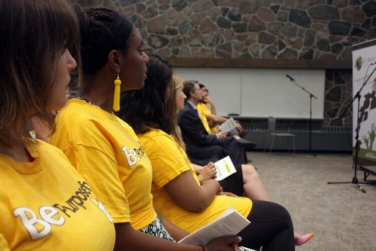 Row of students in yellow tshirts sitting in front row of audience listening to opening remarks