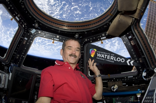 Chris Hadfield in space with a university of waterloo flag