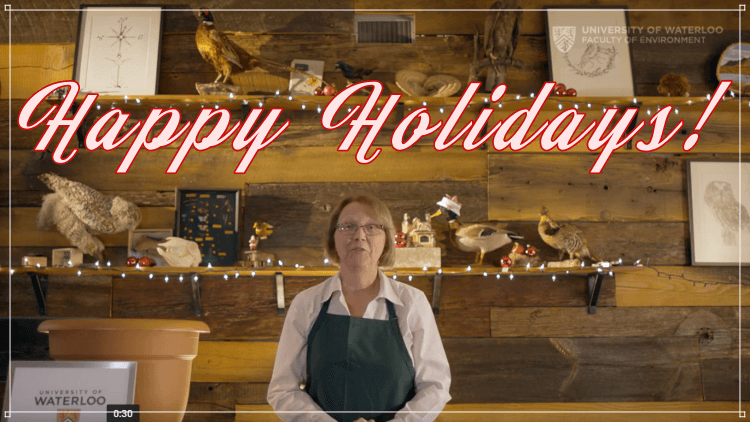 Woman standing at a cooking bench with caption: Happy Holidays